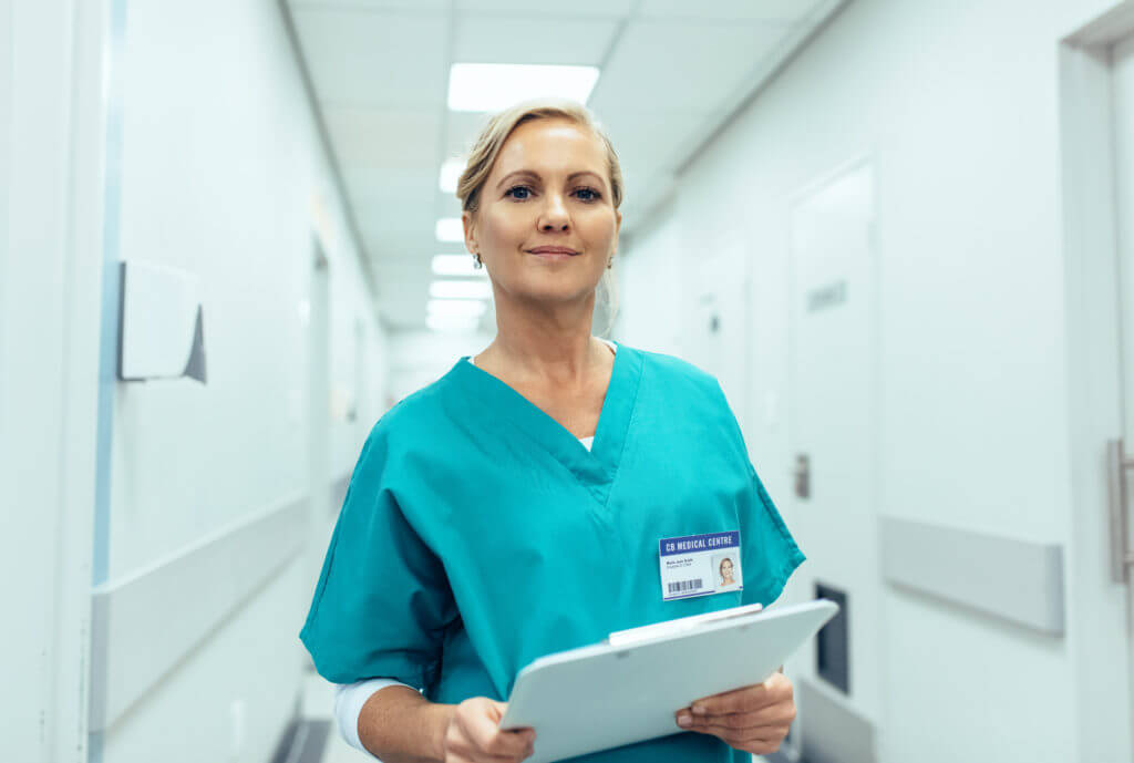 Portrait of mature female nurse working in hospital. Woman healthcare worker with clipboard in corridor.
